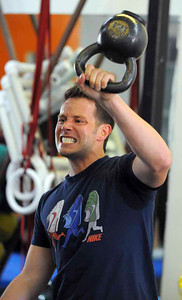 LONG BEACH - 04/24/2010 - (Scott Varley/Daily Breeze) People take part in a Tabata workout at CrossFit Long Beach. Tabata is a workout method where participants exercise at intense levels for 20 seconds followed by 10 seconds of rest for 8 cycles.  James Ulrich tosses a heavy kettle bell above his head. He must do as many reps as he can in the 20 second intervals.
