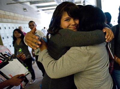 Karla Medellin, an eighth grader at Roy Romer Middle School, embraces one of her teachers as classes end on the final school day of the year at Roy Romer Middle School in North Hollywood on Friday, June 24, 2011.  (Maya Sugarman/Staff Photographer)