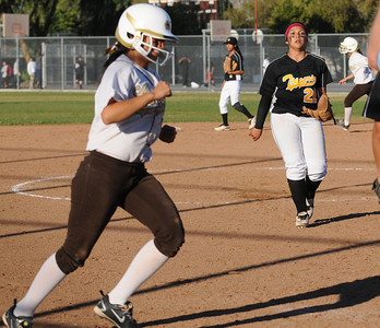 Kennedy Brianna Sotelo walks to the plate to score the winning run as San Fernando Pitcher Daisy Cacho can only watch. The Kennedy girls softball team defeated San Fernando 7-6 in a game played at Kennedy High School in Granada Hills, CA 3/21/2012(John McCoy/Staff Photographer)