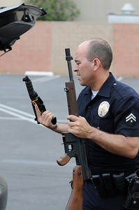 Officer Charles Chacon takes a Tec 9 and Tommy Gun out of the back of a car. The LAPD held their 3rd annual Gun Buy Back program at six locations throughout the city, including the Parking lot at Facey Medical Center on Sepulveda Blvd. in Mission Hills.  The program allows people to anonymously turn in guns to the LAPD and receive a gift card to purchase food at Ralph's grocery stores. A $100 gift card was issued for a handgun; shotgun or rifle while a $200 card was given for weapons classified as assault weapons. Mission Hills, CA 5-7-2011. (John McCoy/staff photographer)