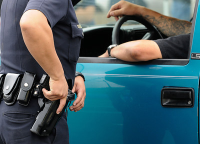 An officer prepairs to go for his side-arm when a man drove up to turn in a weapon that was sitting on the front seat next to him. The LAPD held their 3rd annual Gun Buy Back program at six locations throughout the city, including the Parking lot at Facey Medical Center on Sepulveda Blvd. in Mission Hills.  The program allows people to anonymously turn in guns to the LAPD and receive a gift card to purchase food at Ralph's grocery stores. A $100 gift card was issued for a handgun; shotgun or rifle while a $200 card was given for weapons classified as assault weapons. Mission Hills, CA 5-7-2011. (John McCoy/staff photographer)