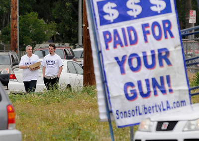 (l-r) Henry Austin and Nick C. hand out maps to a location where people can sell their guns. The LAPD held their 3rd annual Gun Buy Back program at six locations throughout the city, including the Parking lot at Facey Medical Center on Sepulveda Blvd. in Mission Hills.  The program allows people to anonymously turn in guns to the LAPD and receive a gift card to purchase food at Ralph's grocery stores. A $100 gift card was issued for a handgun; shotgun or rifle while a $200 card was given for weapons classified as assault weapons. Mission Hills, CA 5-7-2011. (John McCoy/staff photographer)