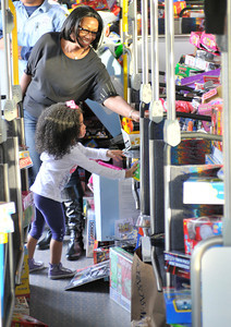 """Hailey Coleman and her grandmother Rosetta Hampton load their toy donation on the bus. Channel 7 weather man Garth Kemp, the Los Angeles Fire Department and Los Angeles Mayor Antonio Villaraigosa participated in a toy drive at the intersection of Topanga Canyon Blvd. and Ventura Blvd. The participants loaded donated toys collected during ABC7's """"Stuff-A-Bus"""" event into two Metro Busses to benefit the LAFD's """"Spark of Love"""" toy drive.  Woodland Hills CA.12-10-2010. (John McCoy/staff photographer)"""