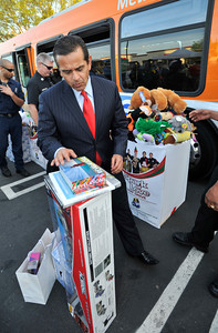 """The Mayor looks at some of the toys that he brought for the toy drive. Channel 7 weather man Garth Kemp, the Los Angeles Fire Department and Los Angeles Mayor Antonio Villaraigosa participated in a toy drive at the intersection of Topanga Canyon Blvd. and Ventura Blvd. The participants loaded donated toys collected during ABC7's """"Stuff-A-Bus"""" event into two Metro Busses to benefit the LAFD's """"Spark of Love"""" toy drive.  Woodland Hills CA.12-10-2010. (John McCoy/staff photographer)"""