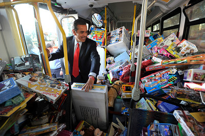 """The Mayor loads toys onto the city bus. Channel 7 weather man Garth Kemp, the Los Angeles Fire Department and Los Angeles Mayor Antonio Villaraigosa participated in a toy drive at the intersection of Topanga Canyon Blvd. and Ventura Blvd. The participants loaded donated toys collected during ABC7's """"Stuff-A-Bus"""" event into two Metro Busses to benefit the LAFD's """"Spark of Love"""" toy drive.  Woodland Hills CA.12-10-2010. (John McCoy/staff photographer)"""