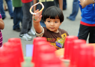 Anthony Rodriguez, -2-years-old, throws rings while playing a game during the North Valley Caring Services Family Fair in North Hills Saturday, April 2, 20011. (Hans Gutknecht/Staff Photographer