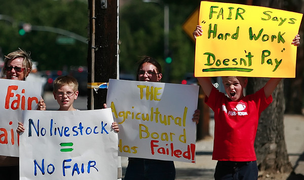 Bodie Stroud, 10, of Sun Valley yells to gain some passer-by support while (L-R) Carolyn Shelton, of Sun Valley, along with Cade Gant, 9, and his sister Rochelle Gant, 16, hold up signs protesting against the San Fernando Valley Fair after having been forced out of the livestock exhibit due to five location changes for the event which ended up in a different county and leaving the children who raised livestock for the fair disappointed. Los Angeles City 7th District Councilmemember Richard Alarcon (not in photo) who was there for a press conference to show support for the group voiced his concerns in front of the main entrance of Saugus Speedway in Saugus, CA, on Thursday, June 7, 2007 as some of the protesters gained support from cars honking their horns while passing by the group. ( John Lazar/L.A. Daily News Staff Photographer )