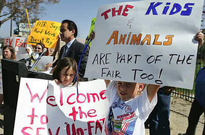 Cassidy Fitzgerald, 8, of Santa Clarita, right, and Clancy Burns, 8, of Sunland, center, hold up their protest signs toward traffic driving by on Soledad Canyon Rd. as Los Angeles City 7th District Councilmemember Richard Alarcon, left, voices his concerns in front of the main entrance of Saugus Speedway during a press conference in Saugus, CA, on Thursday, June 7, 2007 where he stood among young children who were forced out of the San Fernando Valley Fair's livestock exhibit due to five location changed for the event which ended up in a different county at the end leaving the children who raised livestock for the fair empty handed.  ( John Lazar/L.A. Daily News Staff Photographer )
