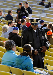 An LAPD Officer talks to fans in the Field Level before the game. Security is at an all-time high at Dodger Stadium in Los Angeles, CA 5-17-2011. (John McCoy/staff photographer)