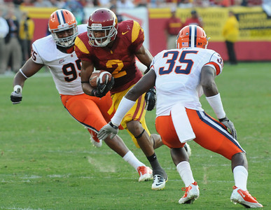 Southern California wide receiver Robert Woods tries to get through Syracuse defensive end (95) Torrey Ball and Syracuse linebacker Dyshawn Davis (35) in the 2nd quarter while driving toward the endzone. The USC Trojans played the Orangemen of Syracuse in a game played at the Coliseum in Los Angeles, CA. 9-17-2011. (John McCoy/Staff Photographer)
