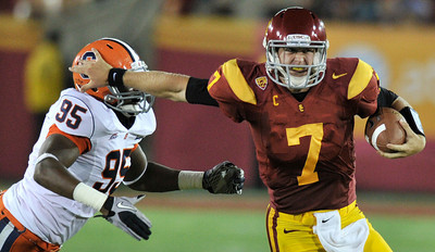 Southern California quarterback Matt Barkley (7) stiff arms Syracuse defensive end Torrey Ball (95) in the 4th quarter. The USC Trojans defeated the Orangemen of Syracuse 38 to 17 in a game played at the Coliseum in Los Angeles, CA. 9-17-2011. (John McCoy/Staff Photographer)