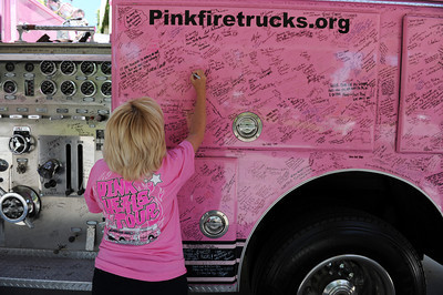 """Donna Ferguson, whose daughter Christy is a cancer survivor,  writes a message on one of the fire trucks from the The Pink Heals Tour. The trucks were at Henry Mayo Newhall Memorial Hospital to show support for women that have been affected by cancer Tuesday, May 10, 2011. The Guardians of the Ribbon"""" are firefighters, police officers and community leaders from around the country dedicated to the fight against all types of cancer affecting women. (Hans Gutknecht/Staff Photographer)"""