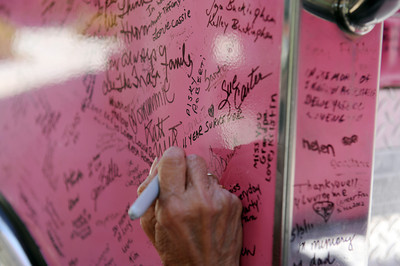 """Cancer survivor Agnes Russell writes a message on one of the fire trucks from the The Pink Heals Tour. The trucks were at Henry Mayo Newhall Memorial Hospital to show support for women that have been affected by cancer Tuesday, May 10, 2011. The Guardians of the Ribbon"""" are firefighters, police officers and community leaders from around the country dedicated to the fight against all types of cancer affecting women. (Hans Gutknecht/Staff Photographer)"""