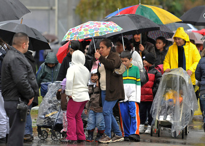 People stand out in the rain waiting for their chance to get toys and other gifts for the holidays. The LAPD Mission Division and LAPD Centurions have partnered with Project Living Hope, several motorcycle clubs and hundreds of volunteers and sponsors to help bring toys, food, entertainment and support to needy children and families in the San Fernando Valley. Thousands gathered at Vista Middle School in Panorama City to allow children to pick out gifts for themselves to celebrate the holidays. Panorama City, CA 12-18-2010. (John McCoy/staff photographer)