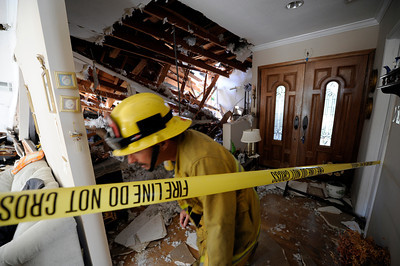 Los Angeles City firefighters tape off a damaged portion of  Seth KhachtourinÕs home.  Khachtourin was in the kitchen of his home at 19657 Hatteras St in Tarzana when a large tree came crashing through the roof from his backyard. ÒIt felt like a 10.0 earthquake,Ó Kahachtourin said as Los Angeles Fire Department personnel moved furniture away from the damaged section of the house. Kahachtourian was home alone when the massive tree fell severely damaging the living and dining rooms Ò it was so loud, it felt like the home was lifted in to the air.Ó  A portion of the home was red tagged by the City of LA Building and Safety because of the risk of further collapse. (Hans Gutknecht/Staff Photographer)