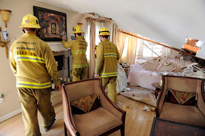 Los Angeles City firefighters move furniture and pictures away from the damaged portion of  Seth KhachtourinÕs home.  Khachtourin was in the kitchen of his home at 19657 Hatteras St in Tarzana when a large tree came crashing through the roof from his backyard. ÒIt felt like a 10.0 earthquake,Ó Kahachtourin said as Los Angeles Fire Department personnel moved furniture away from the damaged section the house. Kahachtourian was home alone when the massive tree fell severely damaging the living and dining rooms Ò it was so loud, it felt like the home was lifted in to the air.Ó  A portion of the home was red tagged by the City of LA Building and Safety because of the risk of further collapse. (Hans Gutknecht/Staff Photographer)Department of Building and Safety because of the risk of further collapse. (Hans Gutknecht/Staff Photographer)