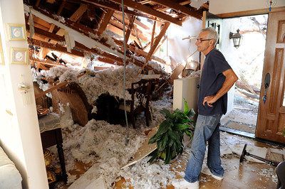 Seth Khachtourin looks at the damage to his home Monday, October 10, 2011.  Khachtourin was in the kitchen of his home at 19657 Hatteras St in Tarzana when a large tree came crashing through the roof from his backyard. ÒIt felt like a 10.0 earthquake,Ó Kahachtourin said as Los Angeles Fire Department personnel moved furniture away from the damaged section of the home. Kahachtourian was in the house alone when the massive tree fell severely damaging the living and dining rooms Ò it was so loud, it felt like the home was lifted in to the air.Ó  A portion of the home was red tagged by the City of LA Building and Safety because of the risk of further collapse. (Hans Gutknecht/Staff Photographer)