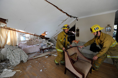 Los Angeles City firefighters move furniture and away from the damaged portion of  Seth KhachtourinÕs home.  Khachtourin was in the kitchen of his home at 19657 Hatteras St in Tarzana when a large tree came crashing through the roof from his backyard. ÒIt felt like a 10.0 earthquake,Ó Kahachtourin said as Los Angeles Fire Department personnel moved furniture away from the damaged section the house. Kahachtourian was home alone when the massive tree fell severely damaging the living and dining rooms Ò it was so loud, it felt like the home was lifted in to the air.Ó  A portion of the home was red tagged by the City of LA Building and Safety because of the risk of further collapse. (Hans Gutknecht/Staff Photographer)Department of Building and Safety because of the risk of further collapse. (Hans Gutknecht/Staff Photographer)
