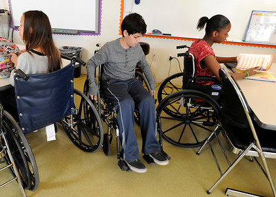 Jamee Riddle,12, Lucas Germain,11, and Akili Moore,11, (all cq) try to negociate the tight spaces in english class. Students at The Country School, a private school in Studio City, have been required to use wheelchairs on campus this week to get a sense of life as a quadriplegic. This is part of a lesson on empathy and overcoming adversity, and in advance of a speaker Friday from the Christopher Reeve foundation. Studio City, CA 3/15/2012(John McCoy/Staff Photographer)