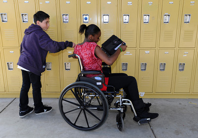 Martin Velasquez,12, help Akili Moore,11, with her locker and books. Students at The Country School, a private school in Studio City, have been required to use wheelchairs on campus this week to get a sense of life as a quadriplegic. This is part of a lesson on empathy and overcoming adversity, and in advance of a speaker Friday from the Christopher Reeve foundation. Studio City, CA 3/15/2012(John McCoy/Staff Photographer)