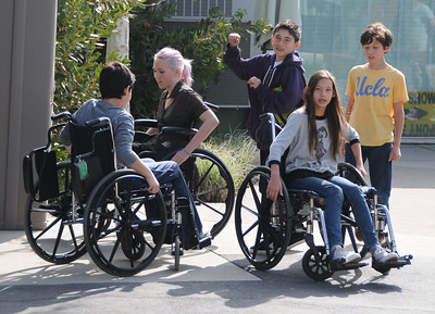 (l-r) in Wheel chairs Lucas Germain, Sadye Hill and Jamee Riddle, hang out with Martin Velasquez, and Milo Hickey, wearing a UCLA shirt. Students at The Country School, a private school in Studio City, have been required to use wheelchairs on campus this week to get a sense of life as a quadriplegic. This is part of a lesson on empathy and overcoming adversity, and in advance of a speaker Friday from the Christopher Reeve foundation. Studio City, CA 3/15/2012(John McCoy/Staff Photographer)