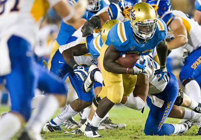 UCLA running back Derrick Coleman pushes through a tackle during a 24-yard run for a touchdown, bringing the Bruins up 27-17. UCLA defeated San Jose State 27-17 on Saturday, Sept. 10, 2011 at the Rose Bowl in Pasadena, Calif. during the Bruins' home opener.  (Maya Sugarman/Staff Photographer)