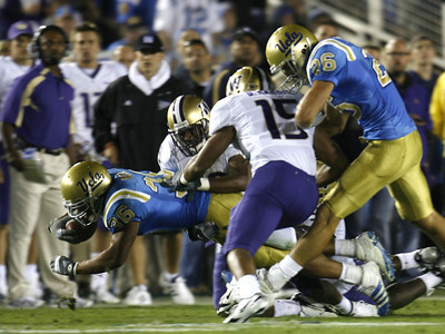 UCLA's Kahlil Bell dives to the ground before getting tackled by Washington defense during the first half on Saturday, September 22, 2007 at Rose Bowl. (Edna T. Simpson)