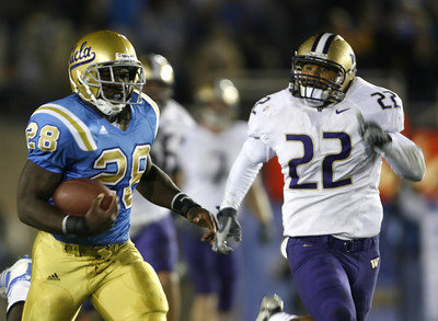 UCLA's Chris Markey gains yardage as he runs ahead of Washington's  E.J.  Savannah during the first half on Saturday, September 22, 2007 at Rose Bowl. (Edna T. Simpson)