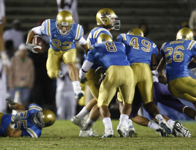 UCla's Michael Norris jumps high in the air to get around Washington defense  during the first half on Saturday, September 22, 2007 at Rose Bowl. (Edna T. Simpson)