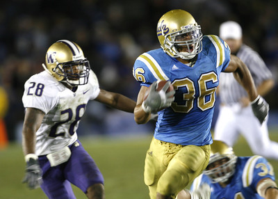 UCLA's Kahlil Bell gains yardage during the fourth quarter as Washington Roy Lewis looks on during the game on Saturday, September 22, 2007 at Rose Bowl. (Edna T. Simpson)