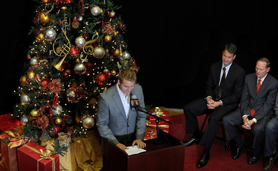 USC Quarterback Matt Barkley gets smiles from his coach Lane Kiffin and Athletic Director Pat Hayden after he announced his decision to stay in school for his Senior year rather than go into the NFL draft. The announcement was made at Heritage Hall, surrounded by Heisman Trophies, and underneath a Christmas tree. Los Angeles, CA 12/22/2011(John McCoy/Staff Photographer)