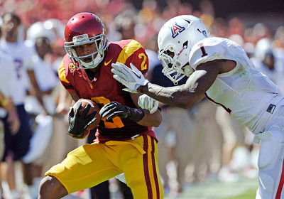 USC's Robert Wood #2 looks for some running room  as Arizona's Robert Golden #1 moves in for the stop defends in the 2nd quarter during their PAC 12 conference game at the Los Angeles Memorial Coliseum in Los Angeles, CA Saturday October 1, 2011. (Hans Gutknecht/Staff Photographer)