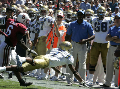 Ucla Brandon  Breazell dives to the sideline in front of Stanford Wopamo Osaisai during the first half of the victory game on Saturday, September 1st, 2007. (Edna T. Simpson)
