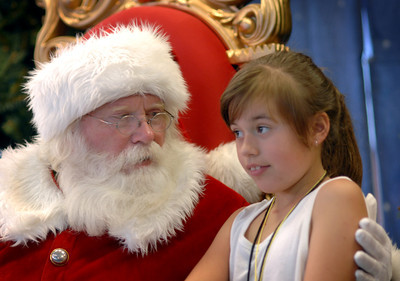 Santa and eight year-old Z'land Nunn, North Hollywood, share a quiet moment berfore photographs.  A 3,000 Pound Holiday Feast Brought Early Holiday Cheer to 1,000 L.A. Area Shelter Families as Universal Studios Hollywood Rang In Its  20th Annual ÒChristmas in SpringÓ Event at M.E.N.D. Transitional Living Center in Van Nuys.  Ten Area Family Shelters in, Hollywood, North Hollywood, East L.A. and Pasadena Facilities Enjoy Festivities with Holiday Feast,  Visit from E.B., Star of ÒHop,Ó  Santa Claus and Scores of Universal Volunteers  2,000 pounds of chicken, 500 pounds of mashed potatoes, 600 pounds of vegetables, 20 gallons of gravy and 6,000 hand-made desserts were served to 1,000 transitional-living family shelter residents during Universal Studios HollywoodÕs 20th annual ÒChristmas in SpringÓ celebration.  For the past 20 years, Universal Studios HollywoodÕs philanthropic ÒDiscover A Star FoundationÓ has helped L.A. Family Housing spread early holiday cheer during this non-traditional time of year when many of the needs of less-affluent families are often overlooked.    E.B., the star of Universal PicturesÕ hit movie, ÒHopÓ Santa Claus, joined Universal Studios Hollywood employee volunteers to bring joy to families and children from M.E.N.D. and those bused in from 10 area transitional living facilities, including P.A.T.H. (People Assisting the Homeless) in Hollywood, L.A. Family HousingÔs North Hollywood Valley Shelter, East L.A.Õs Triangle House, Comunidad Cesar Chavez, Vineland Place in North Hollywood, the Downtown WomenÕs Center in Los Angeles and the Union Station Homeless Services in Pasadena. Dean Musgrove/Staff Photographer