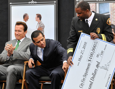 Gov. Arnold Schwarzenegger applauds the donation of $100,000 to the County and City of LA Fire Departments, while Mayor Antonio Villaraigosa attempts to get a better look at the check that was presented to Daryl Osby of the LA County fire department. Universal Studios Hollywood re-opened its backlot that was rebuilt after an extensive fire burned much of it to the ground in June of 2008. Universal City, CA. 5/27/2010. photo by John McCoy/staff photographer
