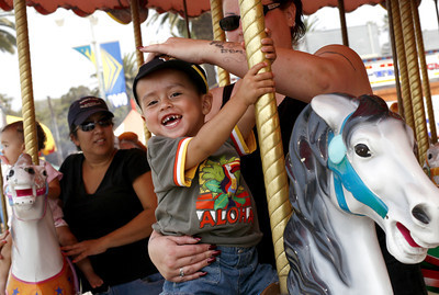 2-year-old Alejandro Garcia from Santa Paula laughs at his father waiting for him to finish the carousel ride at the Ventura County Fair in Ventura, CA. August 4, 2007. (Ernesto Elizarraraz, Special to the Daily News)