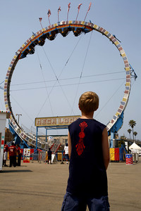 Maybe, maybe not. A boy stares at the thrill ride Mega Loop during the Ventura County Fair in Ventura, CA. August 4, 2007. Mega Loop was one of the big thrill seeking rides featured at the fair. (Ernesto Elizarraraz, Special to the Daily News)