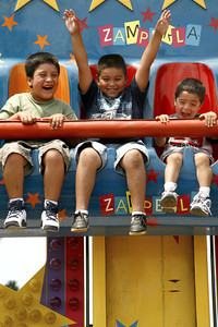 "Thrills. 6-year-old Christian Montoya (center) throws his hands up in excitement in the Zampekla ride which is a kids version of sudden ""free fall"" at the Ventura County Fair in Ventura, CA. August 4, 2007.  (Ernesto Elizarraraz, Special to the Daily News)"