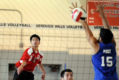 Verdugo Hills' C J Suarez (9) hits the ball as Poly's Kevin Avelar (15) defends during their boys volleyball match at Verdugo Hills High School in Tujunga Monday, April 9, 2012. (Hans Gutknecht/Staff Photographer)