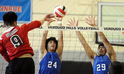 Verdugo Hills' C J Suarez (9) hits the ball as Poly's Ruben Rodriguez (24) and Luis Garcia (29)  defend during their boys volleyball match at Verdugo Hills High School in Tujunga Monday, April 9, 2012. (Hans Gutknecht/Staff Photographer)