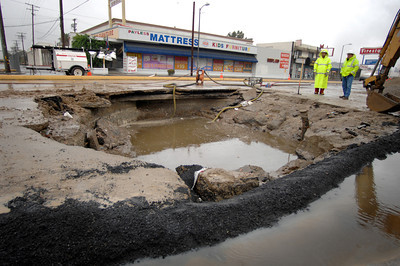 About 25 homes and businesses were without water service this morning in Canoga Park as utility crews tried to make repairs hours after a 12-inch water main broke on Topanga Canyon Boulevard. Crews were still at work near Sherman Way today, a Department of Water and Power spokeswoman said. Street flooding with broken pavement was reported at 9:35 pm, Tuesday in the 7200 block of Topanga Canyon Boulevard.  DWP workers had to build an asphalt berm to prevent rain water from entering the hole.  (Dean Musgrove/Staff Photographer)