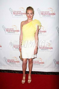 Cat Deely wears a yellow and ivory hand-painted silk linen one-shoulder cocktail dress with a rosette sleeve from Tadashi Shoji's Spring 2012 Runway Collection to the Academy of Television Arts and Sciences College Television Awards in Hollywood on March 31, 2012. Deely accessorizes with Swarovski's silver crystal Pleasure star stud earrings.