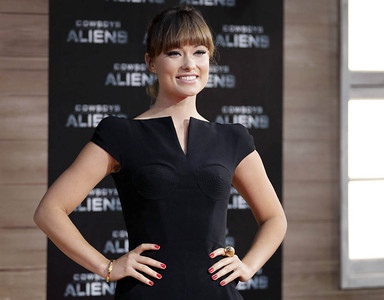 """Actress Olivia Wilde wears a Carrera y Carrera Pasodoble Collection 18K yellow gold bracelet and a Bestiario Collection 18K yellow gold tiger ring with smoked quartz to the """"Cowboys & Aliens"""" premiere in Berlin on Aug. 8, 2011."""