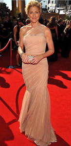 Actress Edie Falco wears Randi Rahm's one-shoulder blush tulle and nude silk Amanda gown to the Primetime Emmy Awards at the Nokia Theatre on Sept. 18, 2011. Falco carries a silver crystal Power clutch by Swarovski.
