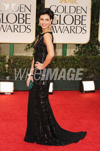Actress Morena Baccarin wears an Edition by Georges Chakra black crepe beaded gown with nude front and back at the Golden Globe Awards in Beverly Hills on Jan. 15, 2012. Baccarin carries Swarovski's emerald green Kiosque clutch.