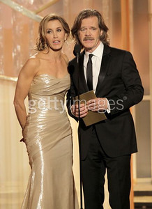 Actress Felicity Huffman, singing with husband William H. Macy, wears Romona Keveza's champagne silk lame chiffon gown with draped one-shoulder neckline and fitted draped bodice and skirt onstage at the Golden Globe Awards in Beverly Hills on Jan. 15, 2012.