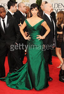 Actress Hannah Simone wears Romona Keveza's emerald mermaid silk shantung taffeta gown with an off-the-shoulder neckline and a ruched train at the Golden Globe Awards in Beverly Hills on Jan. 15, 2012. Simone accessorizes with an Amrapali Victorian rose-cut diamond cuff d rose-cut diamond drop earrings.