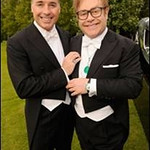 Sir Elton John, right, with partner David Furnish, wears a Chopard pendant with an emerald cabochon, a diamond and emerald watch from the Elton John watch collection, diamond cuff links and one diamond stud to his White Tie and Tiara ball in London on June 23, 2011.