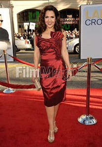 """Actress Maria Canals-Barrera wears David Meister's deep red taffeta strapless dress with draped bodice to the premiere of her film """"Larry Crowne"""" at Grauman's Chinese Theatre on June 27, 2011. Canals-Barrera accessorizes with Swarovski's Lana clutch, Helios desert gold ring and gold crystal Maggy earrings in golden shadow."""