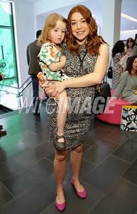 Actress Alyson Hannigan, with her daughter Satyana, wears a Diane von Furstenberg Twisty Clean dress at the premiere of GapKids + DVF Collection at the Grove on March 3, 2012.